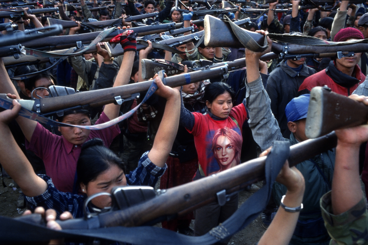 A Maoist rebel soldier wearing a Britney Spears t-shirt stands among a batallion of other soldiers of the People's Liberation Army, First Brigade, Mid Division during a drill in a schoolyard in the village of Gairigaon, Nepal on Wednesday, Feb. 16, 2005.