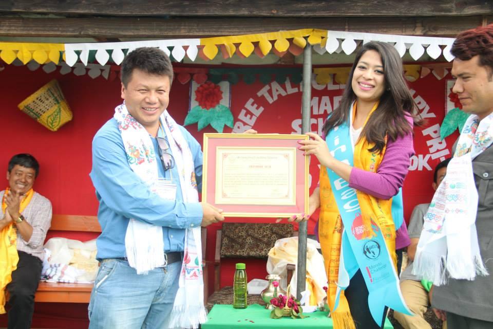 Ishani presents a certificate of appreciation to Jimmy Lama, HELP