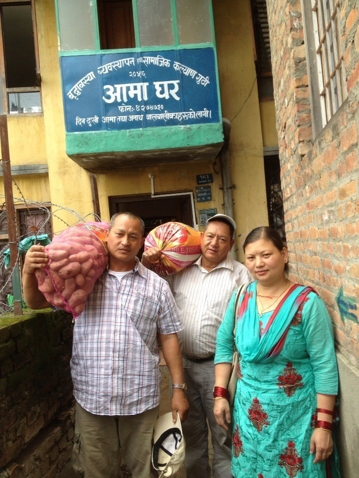 Laxmi's parents and relative carrying goods to donate to Aama Ghar.