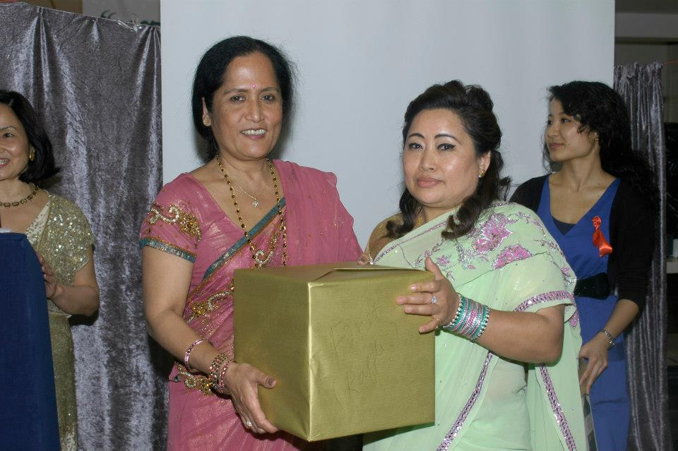 Lucky raffle draw winner being presented with a surprise gift by Dr Rekha Thapa